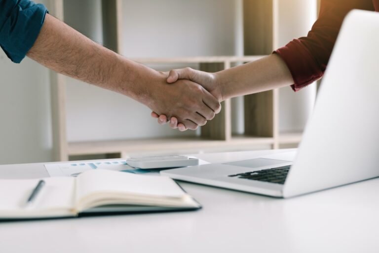 Co-worker startup shaking hands with colleagues in home office.